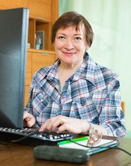 Smiling senior female using keyboard