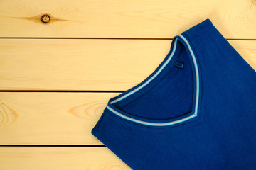 Blue t-shirt on wooden background