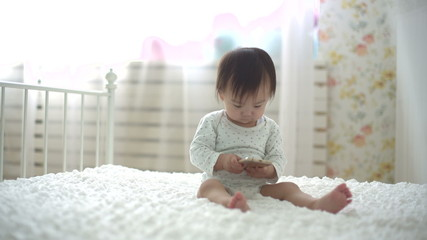 little asian baby sitting and playing with smartphone