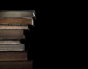Old books in pile on a black background