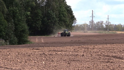 Tractor spread fertilizer on cultivated field in autumn
