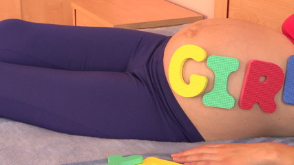 Pregnant woman with girl word on belly lie on bed