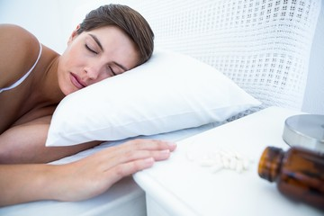 Woman sleeping in bed by spilt bottle of pills
