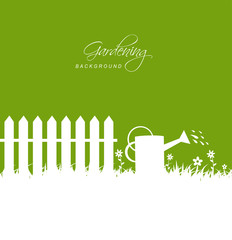 Gardening scene with watering can near fence on grass
