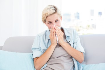 Sick blonde woman blowing her nose