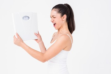 Fit woman holding weighing scales