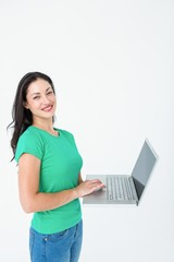 Smiling brunette using laptop