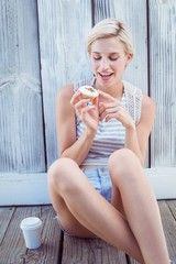Pretty blonde woman holding cupcake