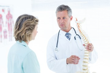 Doctor showing spine models