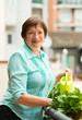 Portrait of elderly woman watering domestic plants