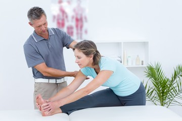 Physiotherapist helping his patient stretching