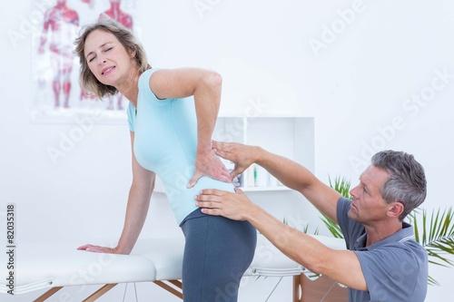 Leinwanddruck Bild Physiotherapist examining his patient back