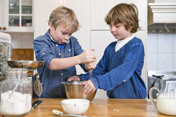 Boys mixing dough in a bowl using a whisk