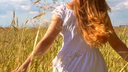 Beauty girl running on yellow wheat field. Happy woman outdoors