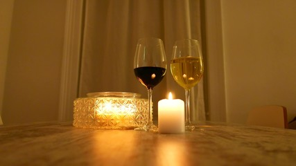 Glasses of red and white wine at candle light
