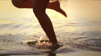 Woman running on beach barefoot over sunset