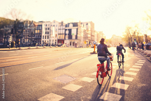 Leinwandbild Motiv Cycling in Amsterdam at Sunset