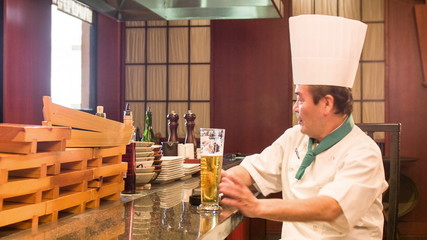 Satisfied Japanese chef sitting in kitchen