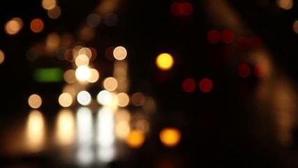 Traffic passes by in the dark night.