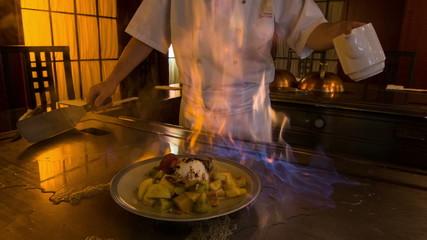 Chef working near big metal hot range in Japanese restaurant