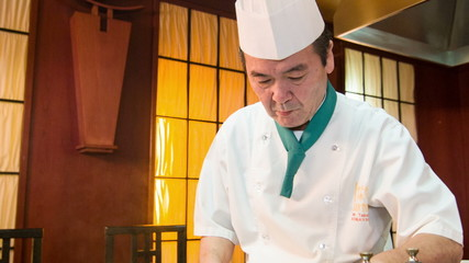 Tracking shot of Japanese chef standing near metal hot plate