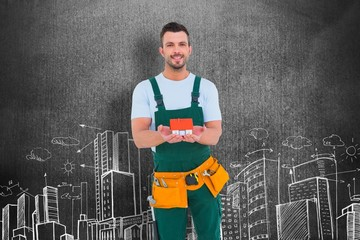 Composite image of happy construction worker holding house model