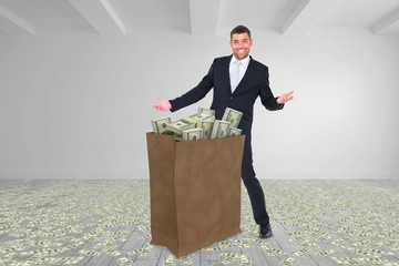 Composite image of businessman carrying bag of dollars