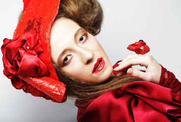 Fashion model in bright red costume and red hat