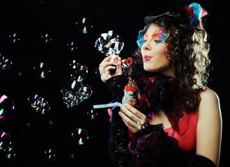 Fashion model blowing soap bubbles.