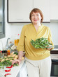 mature woman with okra in  kitchen