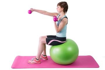 Pretty brunette exercising with dumbbells on fitness ball