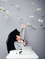 Businessman sitting at the table with rain of money