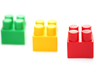 Red lego piece in focus, green and yellow not in focus