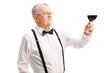 Classy senior gentleman looking at a glass of red wine
