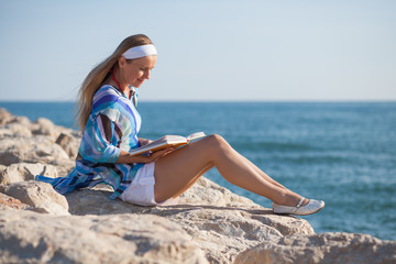 Young woman sitting near sea and reading a book