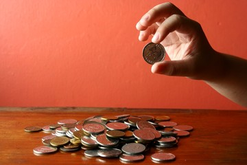 Hand picking a coin from a Bunch of loose change or coins