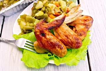 Chicken wings fried with vegetables and salad in plate