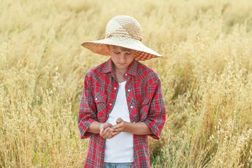 Working farm boy is checking oat seeds in cupped palms at field