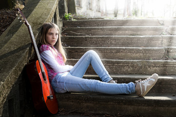 Pensive Girl Sitting on the Stairs While Sun Rays Falling on Her