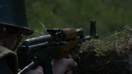 Firing AK 47 assault rifle from trench