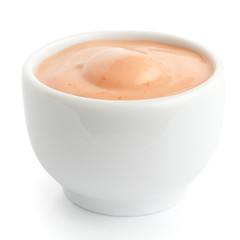Small white ceramic dish of pink dressing. Isolated.