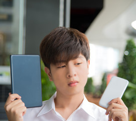 Asian male decide and hesitate to use  smart device