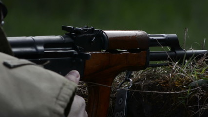 Ak 47 assaul rifle  receiver close up while firing from trench
