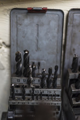Drill bits in old worn metal box in a workshop