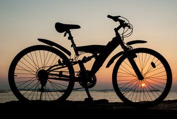 Silhouette of mountain bike parking on jetty beside sea with sun