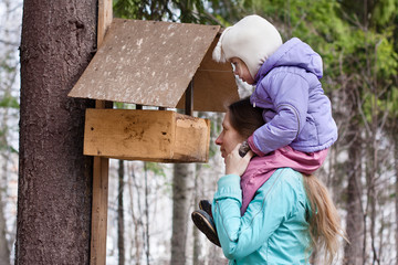 mother shows her daughter the bird feeder