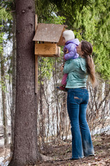 woman shows her daughter the bird feeder