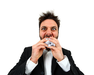 Young angry businessman while eating balled paper.