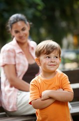 Little kid with mom standing arms crossed