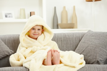 Smiling kid in bathrobe at home sofa bare feet